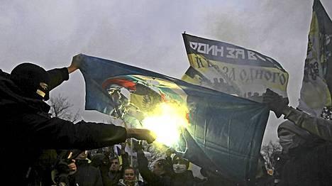 Mellakoitsijat polttavat Yhtenäisen Venäjän lippua mielenosoituksessa Moskovassa