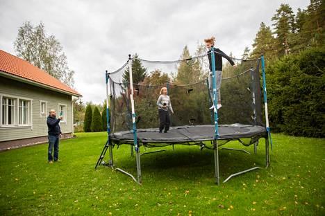 Perheen kaikki lapset viihtyvät takapihan trampoliinilla.