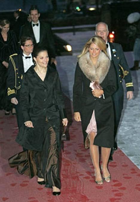 Kruununprinsessa Viktoria ja prinsessa Madeleine saapuvat Haraldin 70-vuotisjuhliin 23. helmikuuta. Madeleinen kohumekko vilkkuu takin alta.