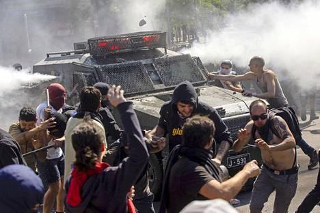 Mielenosoittajat kuvattiin sunnuntaina Santiago de Chilessä heidän ottaessaan yhteen mellakkapoliisin ajoneuvon kanssa.