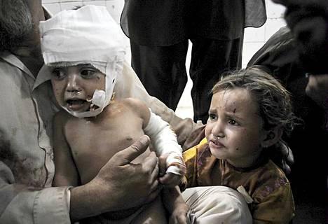 Pakistanilaismies pitää sylissään pommi-iskussa loukkaantunutta lasta sairaalassa Peshawarissa. Pommi tappoi kaksi ihmistä ja 16 haavoittui. Pommi oli asetettu lähelle Panj Peerin rukouspaikkaa tiheästi asutetulle alueelle. Peshawarin kaupunkia on pidetty Talibanin merkittävänä tukialueena ja kaupunki on myös usein yhdistetty Al-Qaedaan.