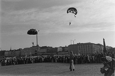 Suomen Laskuvarjokerhon näytöshyppy Helsinki-päivänä Helsingin kauppatorille 12.6.1975. Hyppääjiä oli useampia. Kuvassa näkyvät hyppääjät Einari Mikkonen ja Lauri Oksanen (ylempi hyppääjä) hyppäsivät 1500 metrin korkeudesta ja tulivat maahan hyppääjäryhmän viimeisinä.