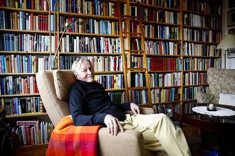 Kirjailija lempihuoneessa kirjojen keskellä.