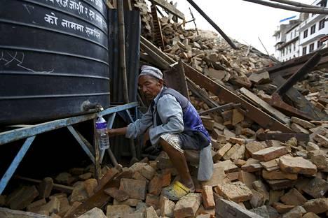 Mies täytti vesipulloaan sortuneen temppelin alueella sijaitsevasta juomavesitankista Kathmandussa sunnuntaina.
