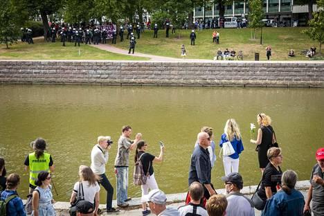 Ihmisiä laskemassa kukkia Aurajokeen 188 Kukkavirta -tapahtumassa. Vastarannalla äärioikeistoa vastustanut mielenosoitus.