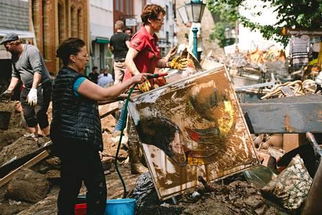 Nainen putsasi mudan peittämää maalausta läntisessä Saksassa lauantaina.