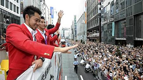 Japanilaisurheiljat tervehtivät kansaa bussin avokatolta.