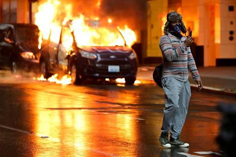 Miehen taustalla palaa poliisiauto. Kuva Seattlesta.