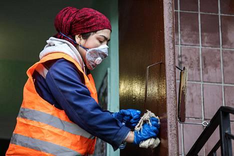 Pietarissa kaupungin työntekijä puhdisti asuintalon ovia koronaviruksen leviämisen estämiseksi.