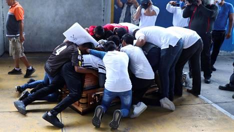 Alexander Martinezin ystävät ympäröivät tämän arkkua 16-vuotiaan jalkapallojuniorin hautajaisissa.