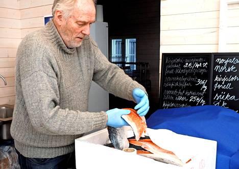 Seppo suolaa lohta savustamossa. Ruuhkaa syntyy, kun uunillinen kalaa valmistuu.
