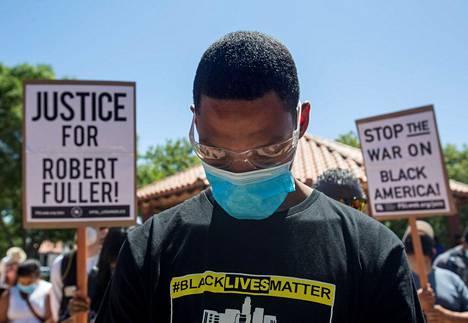 Mielenosoittaja piti minuutin hiljaisen hetken Robert Fullerin muistoksi Palmdalessa lauantaina.