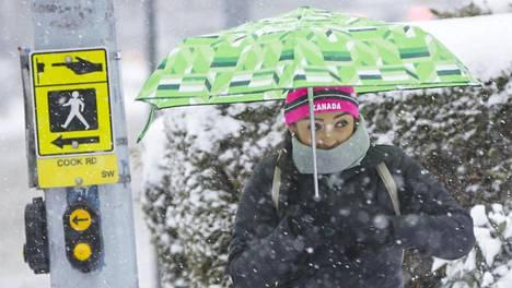 Jalankulkija turvautui lumisateessa sateenvarjoon Kanadan Vancouverissa 24. helmikuuta 2018.