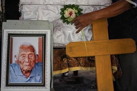 Mbah Gothon haudalle lasketaan kukkaa. Gotho laskettiin haudan lepoon maanantaina.