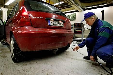 Katsastusmies Jarmo Asikainen asettaa mitta-anturria bensiiniauton pakoputkeen.