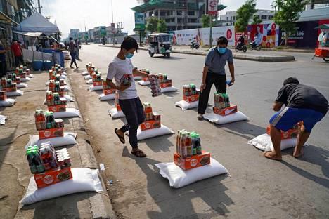 """Vapaaehtoiset järjestelivät Phnomh Penhissä reilu viikko sitten ruoka-apupaketteja jaettavaksi koronasulkuun määrätyn """"punaisen vyöhykkeen"""" asukkaille. Maan hallitusta on syytetty sulkualueiden asukkaiden jättämisestä oman onnensa nojaan."""