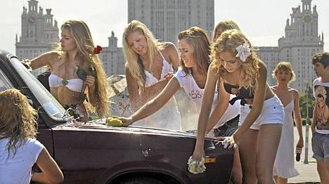 Venäjän pääministerin Vladimir Putinin tukijat pesivät eilen autoja vähissä vaatteissa. Taustalla häämöttää Moskovan yliopisto.