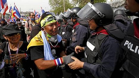 Tunteet nousivat pintaan mielenosoittajalla, joka kätteli poliisia Bangkokissa. osapuolet olivat ottaneet yhteen päiväkausia.