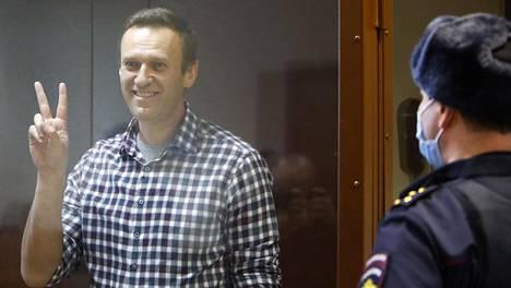 """Aleksei Navalnyi näytti voitonmerkkiä """"akvaariostaan"""" eli syytettyjen lasiseinäisestä kopista lauantaina, kun moskovalainen oikeusistuin käsitteli valitusta hänen ehdollisen tuomionsa muuttamisesta ehdottomaksi."""