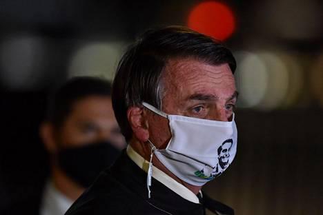 Bolsonarolla nähdään välillä kasvomaski, muttei läheskään aina. Kuvassa hänellä on maski, jossa on kuva presidentistä itsestään.