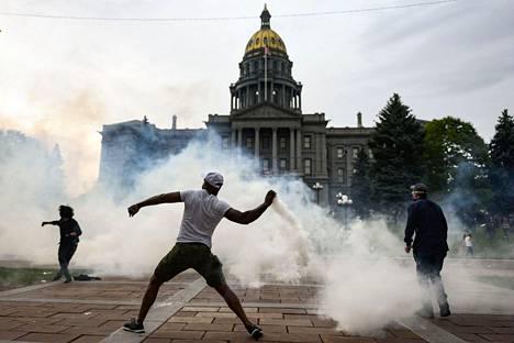 Mies heittää kyynelkaasukanisterin takaisin poliisille Denverissä, Coloradossa. Kuva lauantailta.