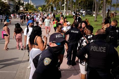 """Poliisit valvoivat järjestystä Miami Beachi Ocean Drive -rantakadulla reilu viikko sitten. Viikonloppuna poliisi hajotti samalla paikalla """"aggressiivisesti ja kurittomasti"""" käyttäytyneen väkijoukon."""
