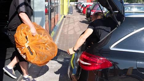 Saka kertoo koronaviruspandemiankin aikaan käytettyjen autojen kaupan olevan vilkasta. Kuvassa renkaat siirtyvät Sakan myymälästä ostetun Mercedes-Benzin tavaratilaan.