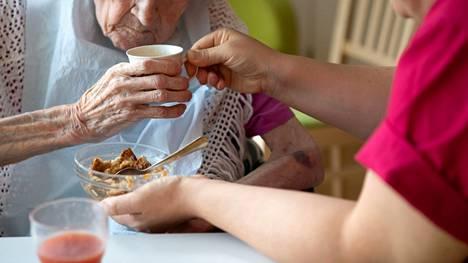 Lähihoitaja avustaa potilasta ruokailussa Espoossa 27. kesäkuuta 2019.