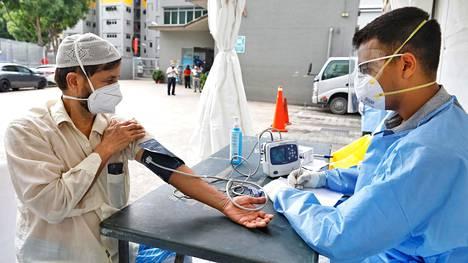 Singaporessa työskentelevä vierastyöläinen kävi terveystarkastuksessa Toh Guanin asuntola-alueella torstaina.