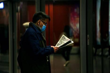 Hongkongilainen mies luki uutisia koronaviruksesta odottaessaan metroa tiistaina.