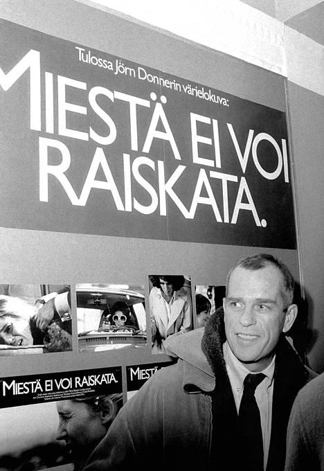 Donner poseerasi ohjaamansa Miestä ei voi raiskata -elokuvan mainosjulisteen edessä 1978.