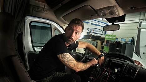 Janne Ahonen asentaa keskittyneesti peruutustutkaa uuteen matkailuautoon lahtelaisessa, oopperalaulaja Mika Pohjosen omistamassa autoliikkeessä.