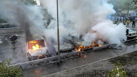 Palokunta sammuttaa palavia autoja Rinkebyn lähiössä Tukholmassa.