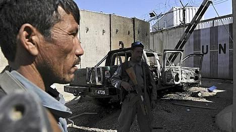 Afgaanipoliisit vartioivat tuhotun YK-keskuksen luona Mazar-i-Sharifissa.