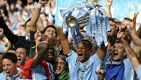 City-kapteeni Vincent Kompany (keskellä kannun kanssa) pääsi nostamaan mestaruuspokaalin sunnuntaina.