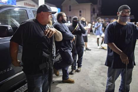 Aseistautuneita miehiä bensa-asemalla Kenoshassa ennen ammuskelua.