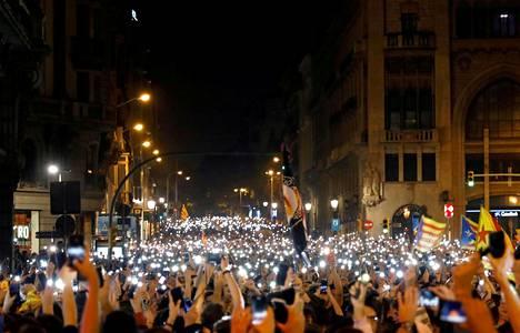 Mielenosoittajat pitivät kännyköitään ylhäällä Barcelonan keskustassa maanantai-iltana.