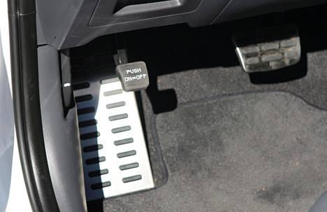 Sähköä hyödyntävässä autossa on mekaaninen seisontajarru. Poljin on sijoitettu hiukan hankalasti jalan lepuutustilan yläpuolelle.