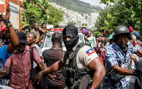 Väkijoukko kerääntyi Port-au-Princen kaduille seuraamaan ja hurraamaan, kun presidentin murhasta epäiltynä kiinni otettuja miehiä kuljetettiin poliisiasemalle.