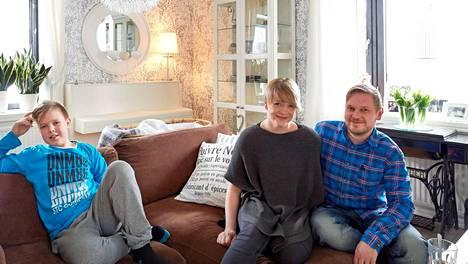 Hanna Talus-Rinne sekä Mikko (oik.) ja Topias Rinne viihtyvät olohuoneen sohvalla.