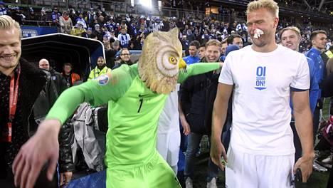 Lukas Hradecky nauratti joukkuetovereitaan Huuhkaja-naamari päässään. Vasemmalla Joel Pohjanpalo, oikealla Paulus Arajuuri tuppo nenässä.
