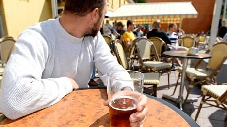 Eräs mies oli oluttuopin kanssa terassilla Helsingissä 22.7.2017.