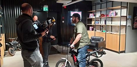 Antti Ilvessuo antaa taidonnäytteen italialaiselle kuvausryhmälle sähköpyörän käytöstä sisätiloissa.