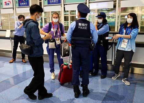 Krystsina Tsimanouskaja poliisien seurassa Tokion Hanedan lentokentällä sunnuntaina.