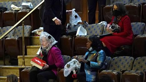Ihmiset odottivat evakuointia kongressin edustajainhuoneen istuntosalissa viime viikon keskiviikkona, kun joukko presidentti Donald Trumpin kannattajia oli jo tunkeutunut sisälle rakennukseen.
