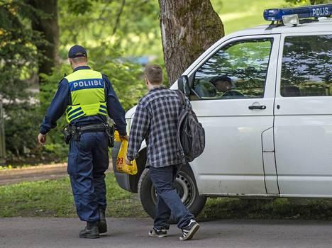 Poliisi tarkastaa Helsingin Alppipuistoon kokoontuneita nuoria. Arkistokuva.