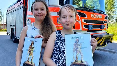 Hertta Ryhänen, 10, (vas.) ja Vilma Hänninen, 9, palkittiin komeilla kunniakirjoilla.