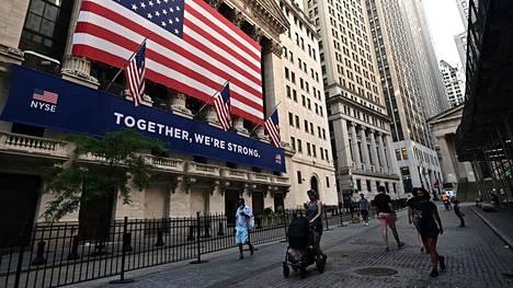 Ihmisiä kävelemässä New Yorkin Wall Streetilla pörssin ulkopuolella.