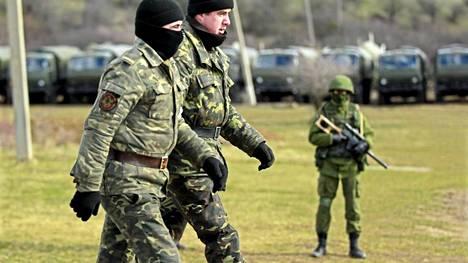 Ukrainalaissotilaat kävelevät venäläissotilaaksi uskotun miehen ohitse Simferopolissa, Krimillä.