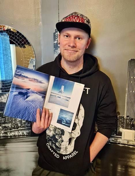 Roni Nieminen esittelee Fotomagazin-lehteä, johon Korson Kulokukkulan kuva painettiin koko sivun kokoisena.